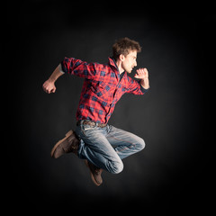 Young man jumping against black background.