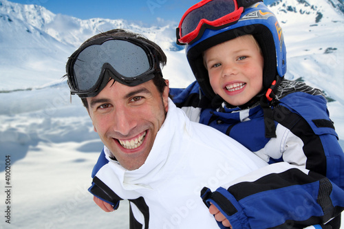Father carrying son on his back at the mountain