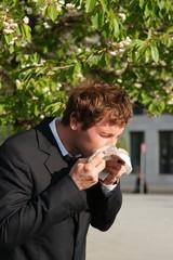 Blütenpollenallergie - Geschäftsmann niest ins Taschentuch