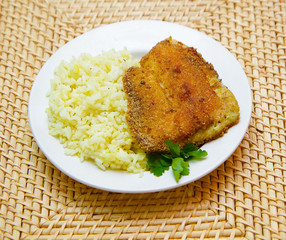 fried tilapia with rice garnish on a white plate