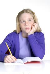 Niña de regreso a clases escribiendo y pensando.