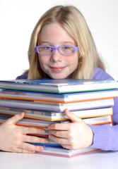 Niña de regreso a clases sujetando unos libros.
