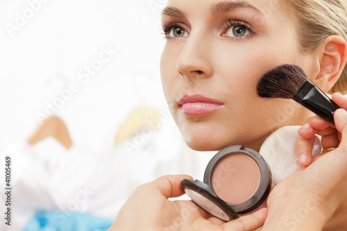 Using blush brush to apply blush on cheeks