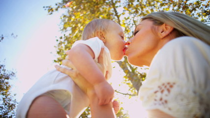 Young Mom Kissing Baby Son Outdoors