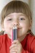 Niña contenta sujetando unos lápices de colores.
