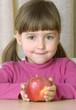 Pequeña niña comiendo una manzana roja.