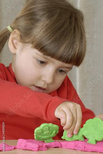 Niña jugando con plastilina.