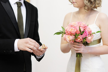 Groom holding ring during wedding ceremony