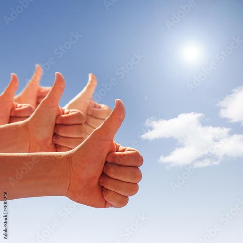 Männerhände zeigen Daumen hoch am blauen Himmel