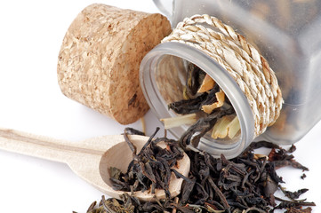 Tea leaves in transparent parison with wooden spoon