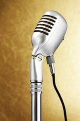 Retro style microphone. Gold background