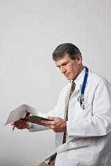 Male Doctor Reviewing Patient Notes or Records