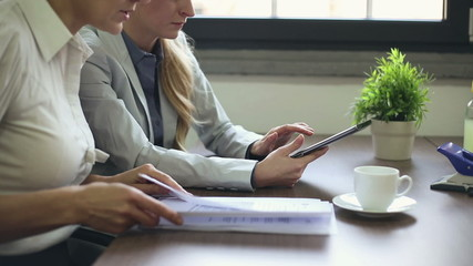 Businesswomen working with documents and tablet computer