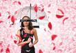 Pretty woman under umbrella with petals around her