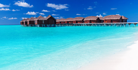 Overwater villas in blue tropical lagoon with white beach