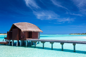 Overwater villas in blue lagoon of an island