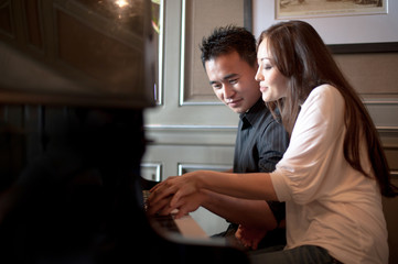Attractive Asian Couple playing piano