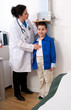 Female doctor measuring height of a child patient in clinic