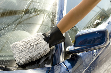 Close-up of a man cleaning a car with sponge