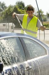 Young man working at car wash station