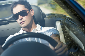 Young man driving his convertible car