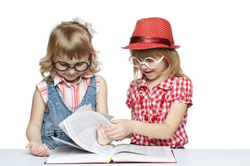 Two little girls in funny eyeglasses reading book