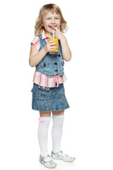 Little girl licking finger holding glass with orange juice