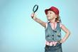 Leinwanddruck Bild - Little girl with magnifying glass, isolated on blue