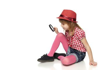 Full length of little girl sitting on floor with magnifier