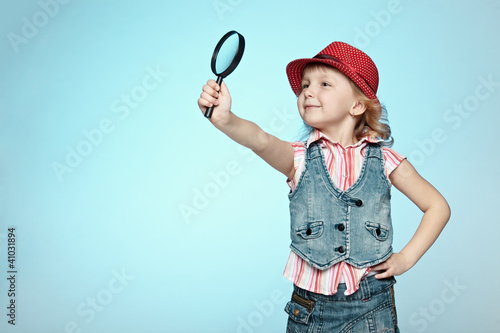 Little girl with magnifying glass, isolated on blue