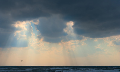 Sun behind dark storm clouds over the sea