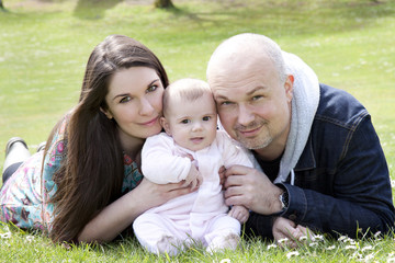 family of three in park with baby