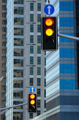 Two traffic lights against background of modern buildings.