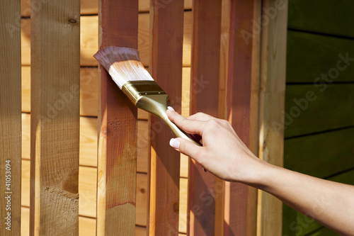 woman's hand with a paint brush painting wooden terrace in pink