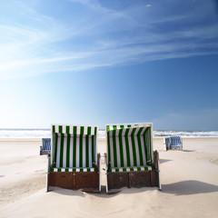 green beach chairs on a deserted sunny beach