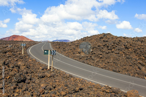 Road through lava rocks and volcanic mountains. Los Hervideros.
