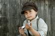Junge vor einer Holzwand