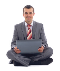 Happy young business man working on a laptop