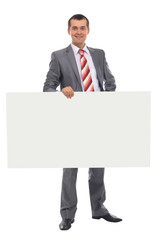 Happy smiling young business man showing blank signboard
