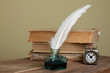 Quill, inkwell, old books, vintage clock on wooden table