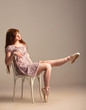 Redhead girl trying on pointe shoes while sitting on a chair