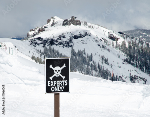 Sign with skull and bones designating experts only skiing area