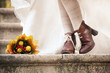 colorful autumn bouquet and two women legs with leather boots