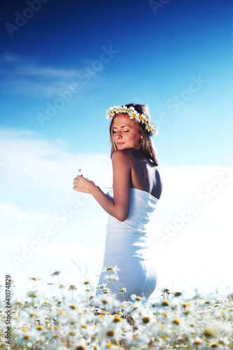 girl in dress on the daisy flowers field