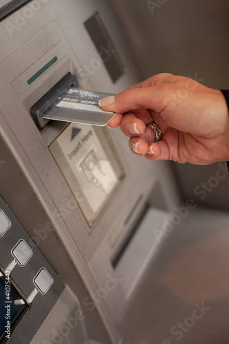 Female hand inserting ATM card