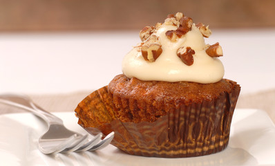 Delicious carrot cake cupcake with cream cheese frosting and nut