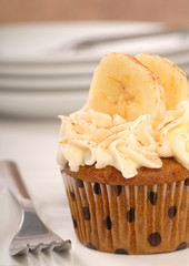 Vanilla cupcake with cream cheese frosting and sliced bananas