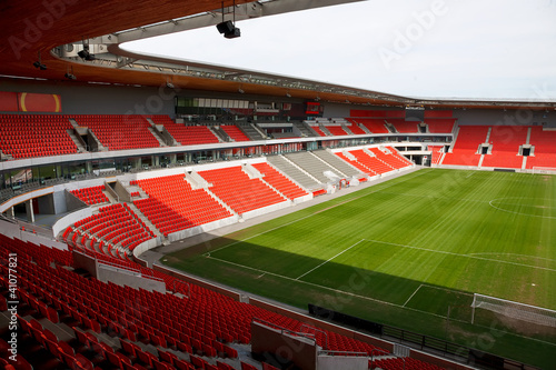 View on an empty football (soccer) stadium with red seats