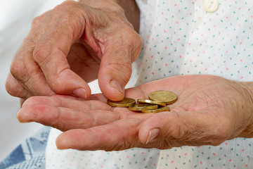 Hands of an old woman with coins