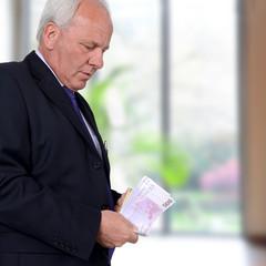 Älterer Herr mit Geldscheinen